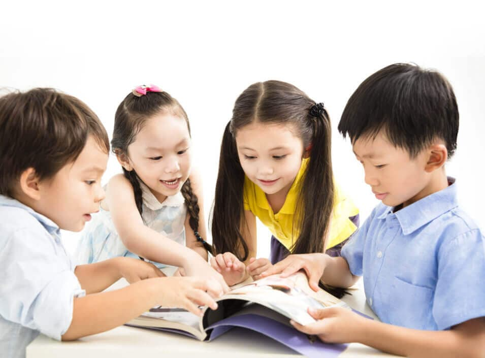 cute little kids looking at the book