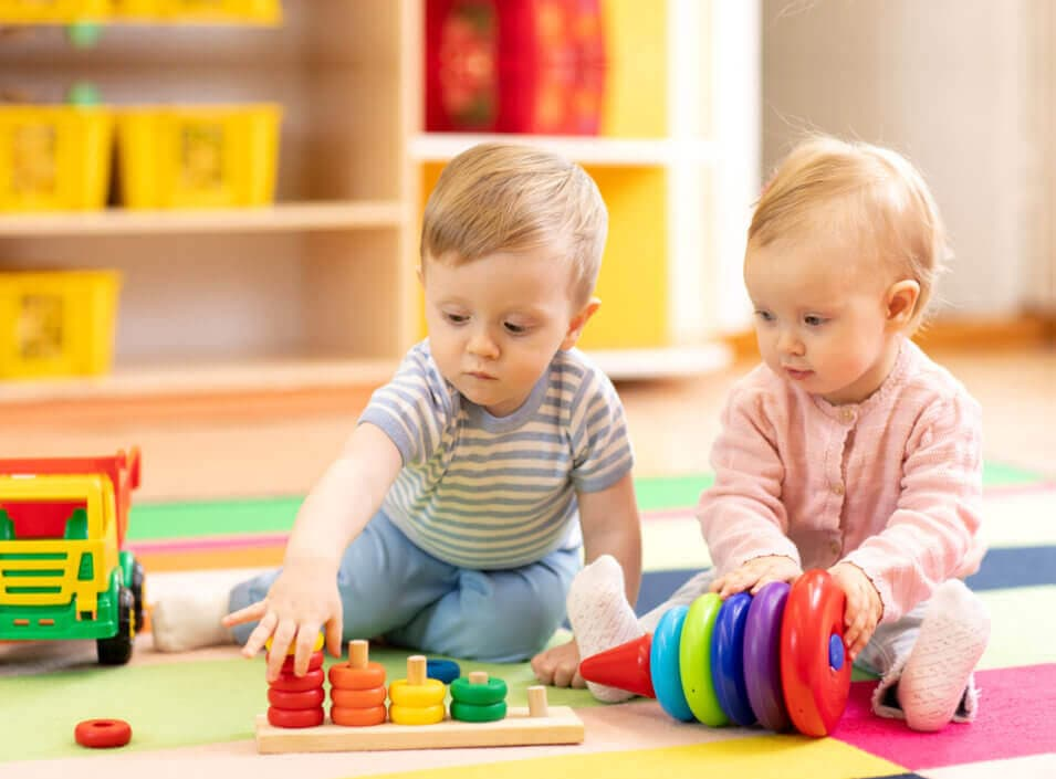 Preschool boy and girl playing on floor with educational toys.