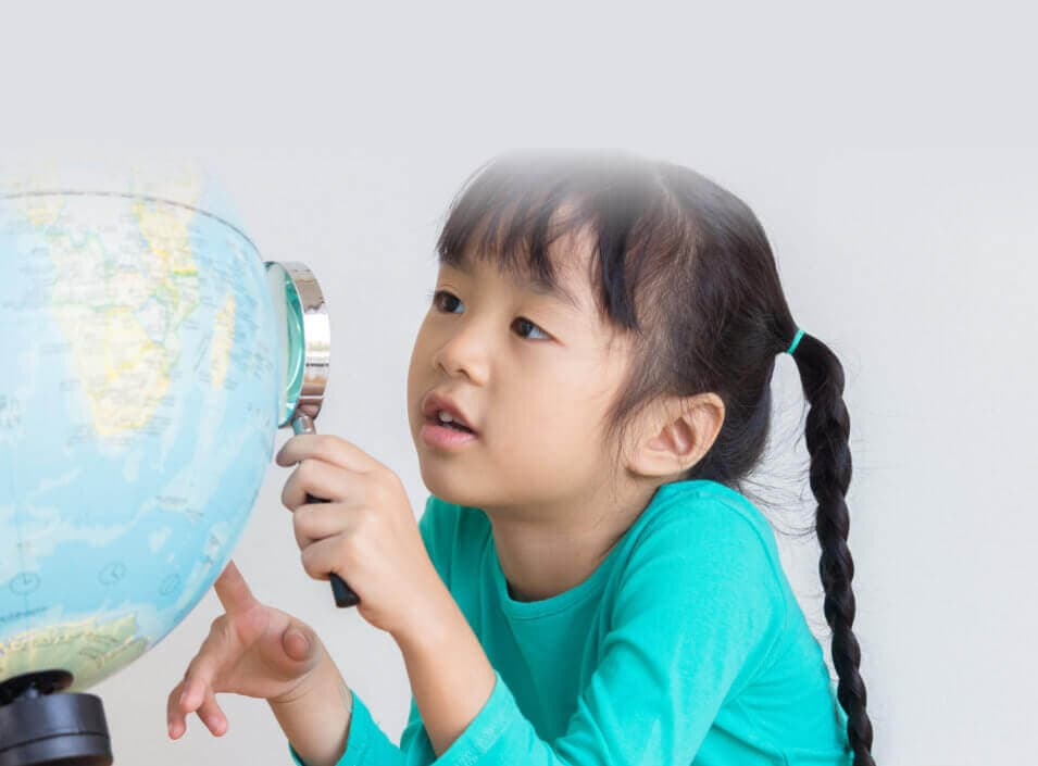 cute young girl looking at the globe