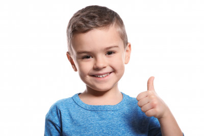little boy showing thumb up gesture in sign language