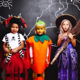 three cute little girls wearing costumes