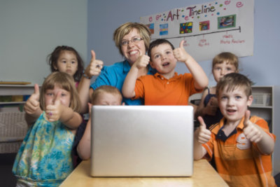 children and teacher play and learn while using a laptop computer at the preschool class