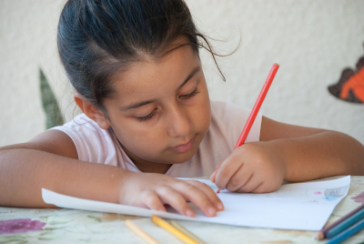child coloring in a drawing with colorful pencils