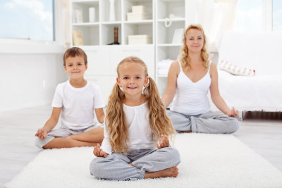 kids doing yoga relaxing exercise with their trainer