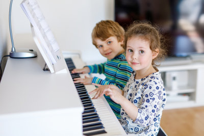 two little kids playing piano